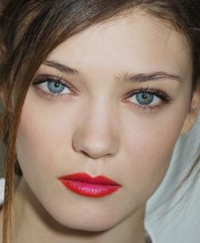 Os lábios são inteiros contornados por um vermelho aberto. No centro, pinceladas de rosa